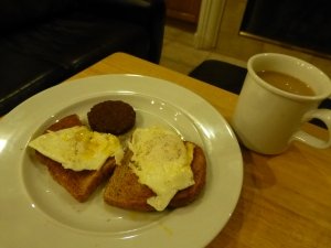 Two over-easy eggs on toast, a snausage and a cup of tea