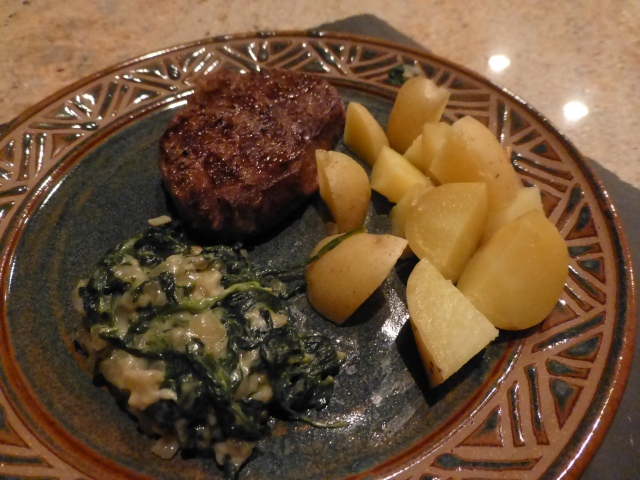 Grilled rib eye steak with steamed potatoes and creamed spinach