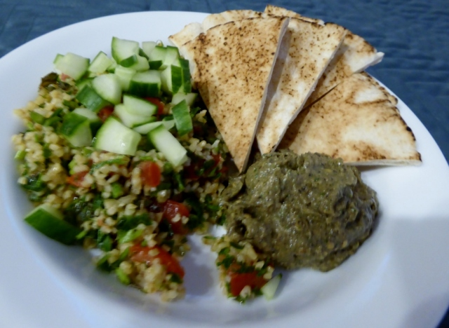 (Sorry for the blurriness) Tabbouleh topped with chopped cucumbers, baba ganoush and pita