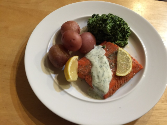 Sous vide salmon with dill-yogurt sauce, steamed potatoes, and spinach.