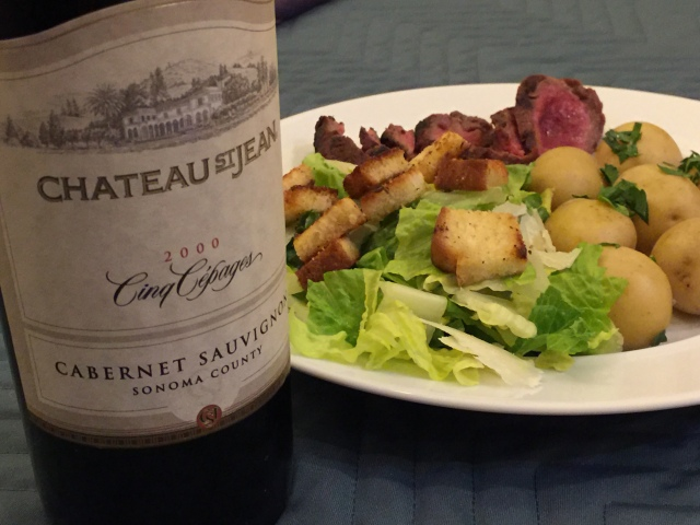 Grilled rib eye steak with steamed new potatoes and Caesar salad served with a 2000 Chateau St. Jean Cinq Cepages