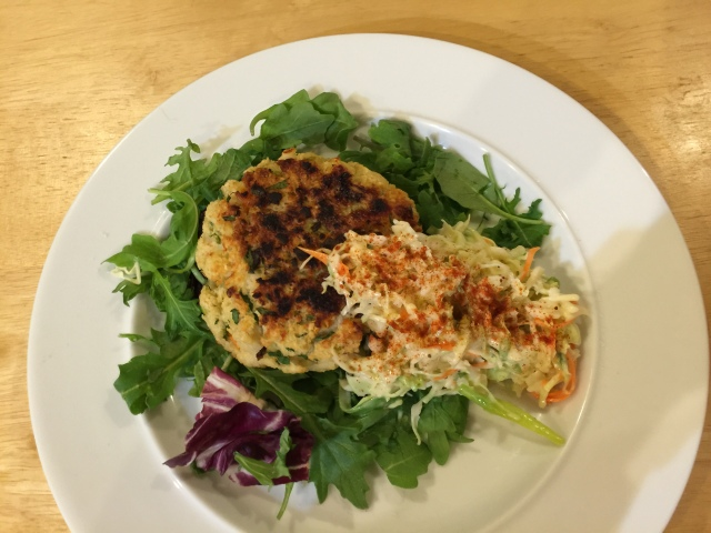 Seafood cake with spicy coleslaw and greens
