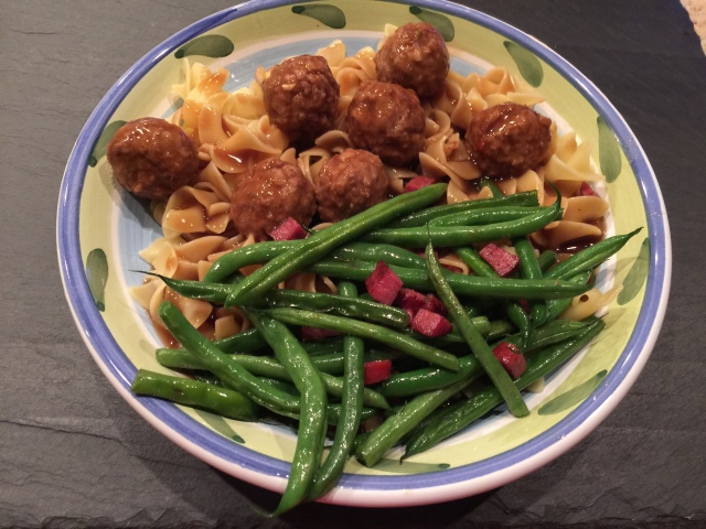 Meatballs and gravy over noodles with green beans