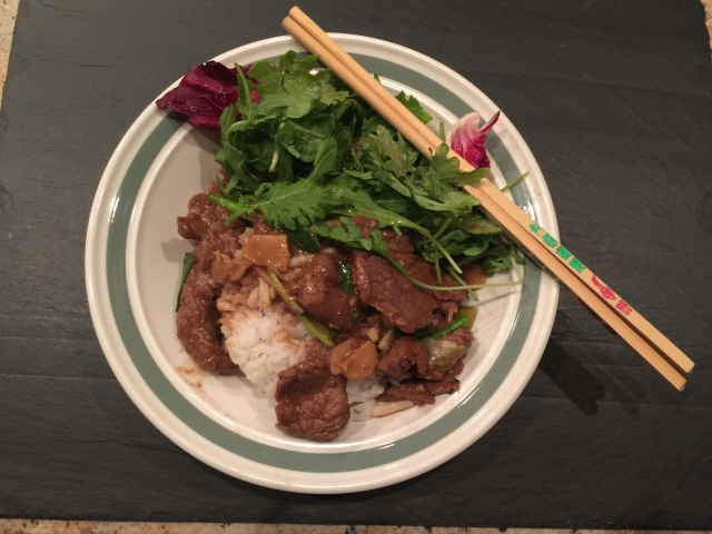 Mongolian beef served over rice with a green salad