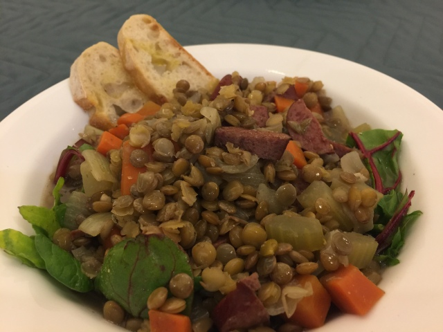 Lentil stew with carrots and turkey sausage on kale